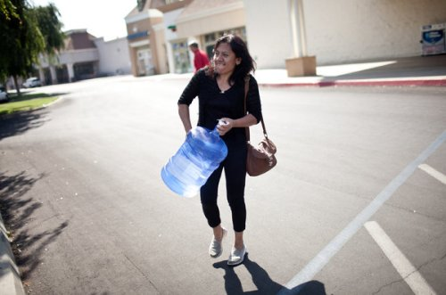 Laura Garcia in Monson CA carries a water bottle