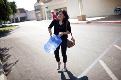 Laura Garcia in Monson CA carries a water bottle